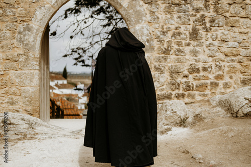 Black hooded monk wearing long cloak walking on middle ages European street Fotobehang