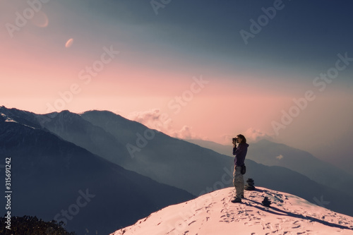 Traveller photographer relaxing on top of snow high mountain and enjoying view o Wallpaper Mural