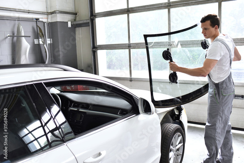 Photo mechanic in a garage replaces defective windshield of a car