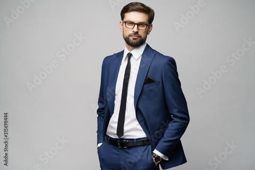 Fototapeta studio photo of young handsome stylish businessman wearing suit obraz