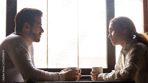 Photo Millennial couple talking in cafe drinking coffee