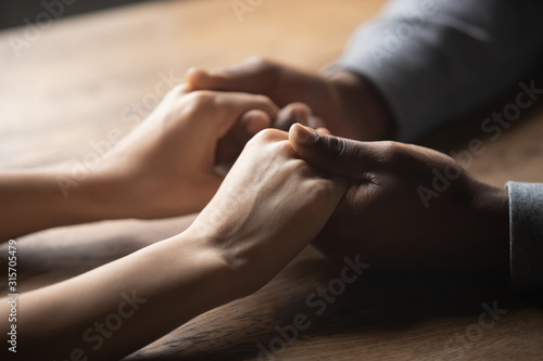Close up of multiracial couple holding hands in cafe Canvas Print