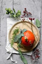 Red Kuri Squash (Cucurbita Maxima), Rosemary, Rose Hips, Sage, Napkin And Wooden Plate