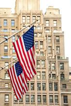 USA, New York, New York City, American Flags Hanging Against Skyscraper
