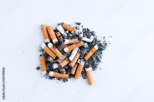 Obraz na plátne Cigarette butts with a yellow filter near a pile of ash on a white background