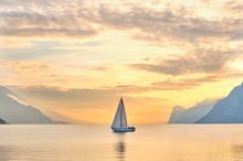 Italy, Trentino, Nago-Torbole, Sailboat Sailing Near Coastal Cliffs Of Lake Garda At Moody Dawn