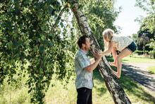 Father Helping Daughter Climbi...