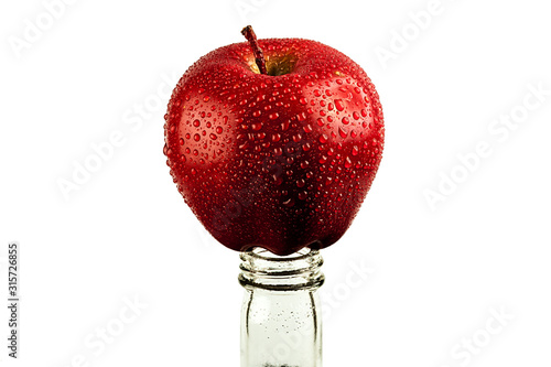 Photo red Apple in drops of water on the neck of the bottle