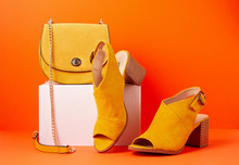 Yellow Female Fashion Accessories, Shoes And Handbag Over Orange Background. Beauty, Shopping, Urban Outfit And Fashion Trends