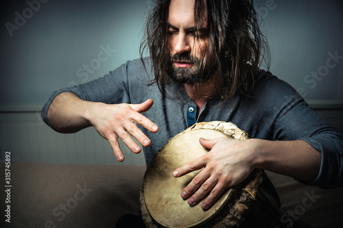 Leinwand Poster Long-haired man playing an ethnic percussion musical instrument jembe