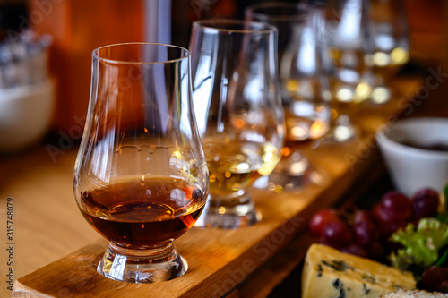 Scotch whisky, tasting glasses with variety of single malts or blended whiskey spirits on distillery tour in Scotland