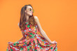 canvas print picture - Girl in floral dress emotionally poses on the orange background.
