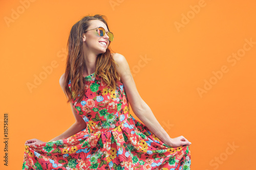 Fotografía Girl in floral dress emotionally poses on the orange background.