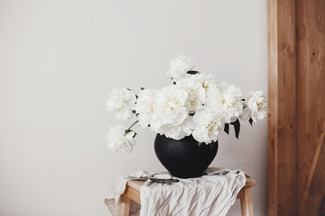 White peonies rural still life. Stylish peony bouquet in black clay vase on linen fabric with scissors on rustic background.Hello spring wallpaper. Happy Mothers day. Space text