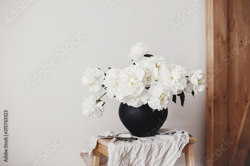 Fototapeta  White peonies rural still life. Stylish peony bouquet in black clay vase on linen fabric with scissors on rustic background.Hello spring wallpaper. Happy Mothers day. Space text obraz
