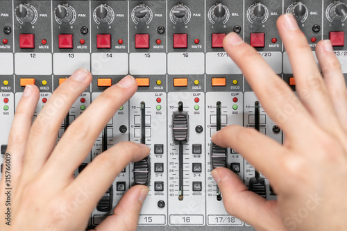 Photo Close-up of a mixing console, hand equalizing audio channels