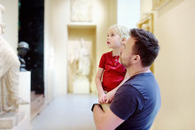Little Boy With His Father Looking At Sculptures.