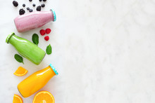 Assorted Healthy Smoothies In Bottles With Ingredients. Top View Side Border Against A White Marble Background. Blueberry, Green And Orange. Copy Space.