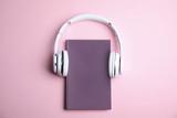 Fototapeta Kawa jest smaczna - Book and modern headphones on pink background, top view