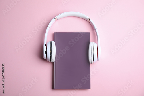 Book and modern headphones on pink background, top view