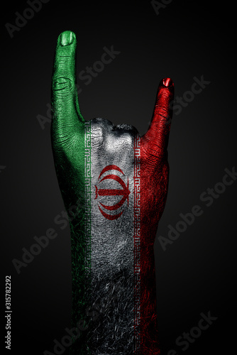 Fotomural A hand with a drawn Iran flag shows a goat sign, a symbol of mainstream, metal and rock music, on a dark background