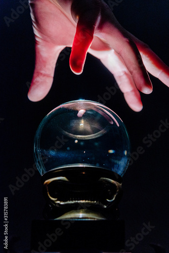 Fotografie, Obraz Hand over crystal ball in dark room, crystal ball gazing, crystal ball psychic,