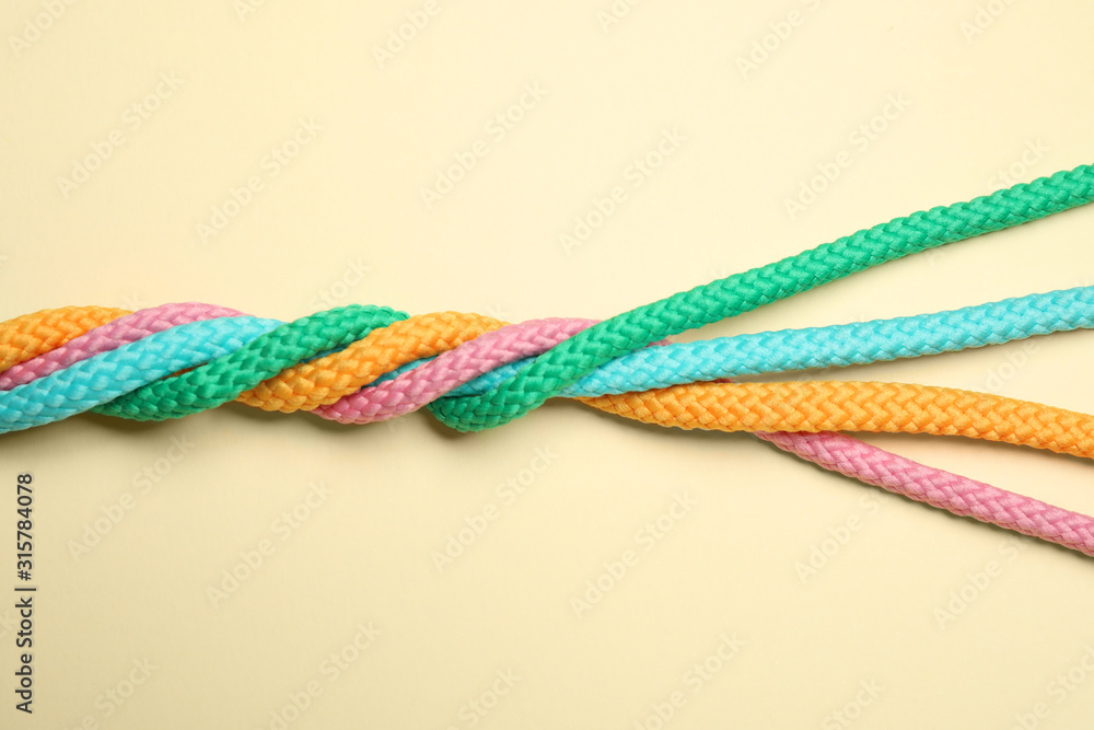 Fototapeta Twisted colorful ropes on beige background, top view. Unity concept