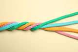 Fototapeta Kawa jest smaczna - Twisted colorful ropes on beige background, top view. Unity concept
