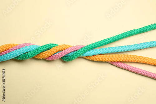 Obraz Twisted colorful ropes on beige background, top view. Unity concept - fototapety do salonu