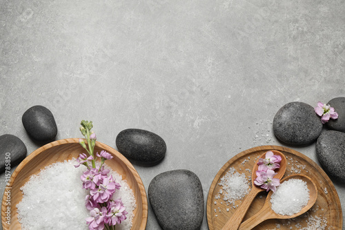 Flat lay composition with sea salt and spa stones on grey marble table. Space for text