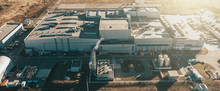 Aerial Panoramic View Of Industrial Factory Or Warehouse Modern Building In Sunlight, Drone Point Of View.