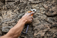A Close Up Shot On The Muscular Arm Of A Caucasian Male, Fixing A Belay Rope Anchor Point Into A Rugged Limestone Crag During Rock Climbing Adventure