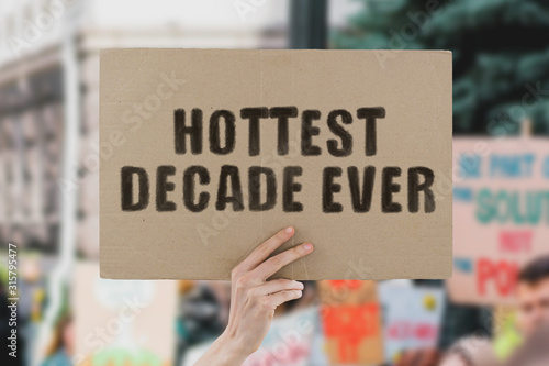 The phrase  Hottest decade ever  on a banner in men's hand Tablou Canvas