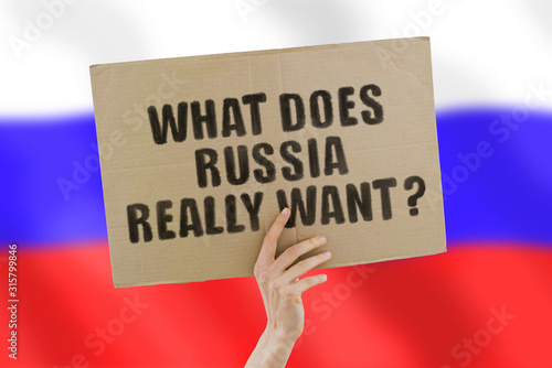 Photo  The phrase  What does Russia really want?  on a banner in men's hand with blurred Russian flag on the background