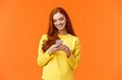 canvas print picture - Communication, people and chat concept. Carefree modern hipster girl edit photos with filters on smartphone application, use app for chatting, smiling as looking mobile display, orange background