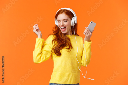 Technology, emotions and gadgets concept. Cheerful good-looking redhead woman dancing with hands up, closed eyes, smiling joyfully, enjoy awesome music sound in headphones, hold smartphone