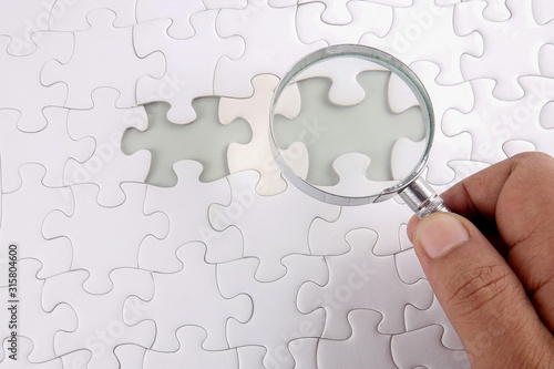 Photo Magnifying glass searching missing puzzle.
