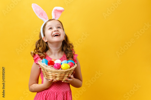 Carta da parati Beautiful cute little girl in Easter bunny ears holds a basket with eggs on a yellow background
