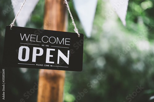 Obraz Open sign hanging on tree with green nature bokeh sunlight background. - fototapety do salonu