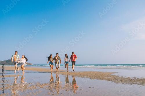 Fototapeta A group of happy friends who play fun on the white sand beach amid the blue sky.. obraz na płótnie