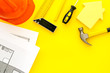Leinwanddruck Bild - Construction concept. Helmet, tools on work desk, house cutout on yellow background top-down frame copy space