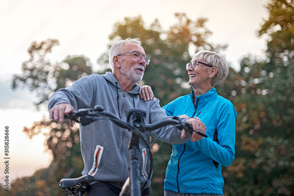 Fototapeta Older couple in park, he is with bicycle and she walk beside and talking