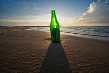 Beer Bottle On A Sandy Beach With Clear Sky And Wave
