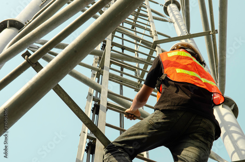 Photo engineer wear safety equipment and climb high telecom tower work for maintenance working