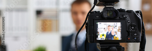 Obraz Male in suit and tie show confirm sign arm making promo videoblog or photo session in office camcorder to tripod closeup. Vlogger promotion selfie solution or finance advisor management information - fototapety do salonu