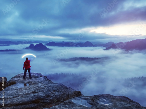 Girl traveler stands on top of mountain holding strong light Canvas Print
