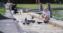 Happy Girl Blonde Feeds Pigeon...