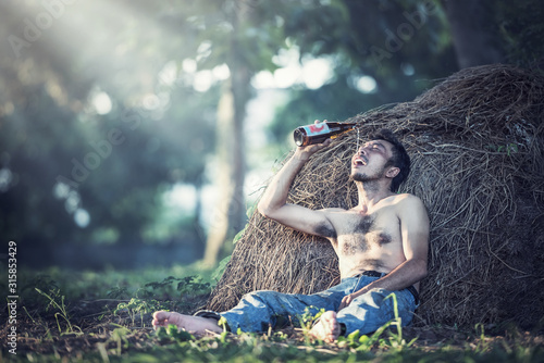 Alcohol addicted man sitting alone with alcohol bottle Canvas-taulu