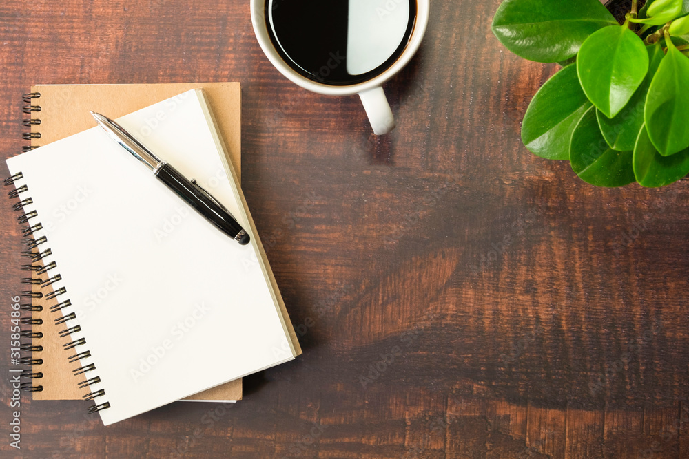 Fototapeta Top view of open school notebook with blank pages, Pen, Plant and Coffee cup on wooden table background. Business, office or education concept with copy space.