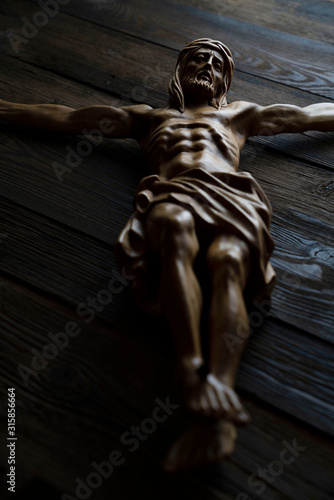 Fotomural Cruciefied Jesus figure isolated on rustic dark brown table.